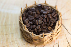 Μαύρα σιτάρια καφέ σε ένα εκλεκτής ποιότητας ψάθινο καλάθι σε ένα ξύλινο υπόβαθρο Στοκ εικόνα με δικαίωμα ελεύθερης χρήσης