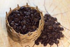 Μαύρα σιτάρια καφέ σε ένα εκλεκτής ποιότητας ψάθινο καλάθι σε ένα ξύλινο υπόβαθρο Στοκ Φωτογραφία