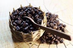 Μαύρα σιτάρια καφέ σε ένα εκλεκτής ποιότητας ψάθινο καλάθι σε ένα ξύλινο υπόβαθρο με ένα ξύλινο κουτάλι Στοκ Φωτογραφίες
