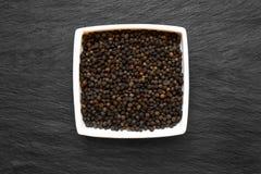 Μαύρα σιτάρια πιπεριών στο άσπρο πιάτο που τοποθετείται στη μαύρη πέτρινη επιφάνεια υποβάθρου στοκ φωτογραφία με δικαίωμα ελεύθερης χρήσης