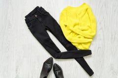Μαύρα τζιν, κίτρινο πουλόβερ και μαύρα παπούτσια στο ξύλινο υπόβαθρο Στοκ εικόνες με δικαίωμα ελεύθερης χρήσης