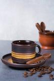 Μαύρα arabica φλυτζάνι καφέ και φασόλια καφέ στο γκρίζο πνεύμα υποβάθρου Στοκ Εικόνα