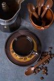 Μαύρα arabica φλυτζάνι καφέ και φασόλια καφέ στο γκρίζο πνεύμα υποβάθρου Στοκ Φωτογραφίες