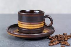 Μαύρα arabica φλυτζάνι καφέ και φασόλια καφέ στο γκρίζο υπόβαθρο Στοκ Εικόνα