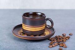 Μαύρα arabica φλυτζάνι καφέ και φασόλια καφέ στο γκρίζο υπόβαθρο Στοκ Εικόνες