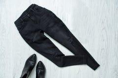 Μαύρα ragged τζιν και μαύρα παπούτσια στο ξύλινο υπόβαθρο Μόδα Στοκ εικόνες με δικαίωμα ελεύθερης χρήσης