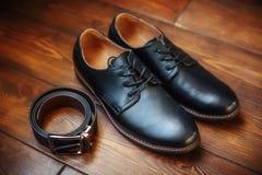 Μαύρες αρσενικές παπούτσια και ζώνη δέρματος στο ξύλινο υπόβαθρο Στοκ φωτογραφία με δικαίωμα ελεύθερης χρήσης
