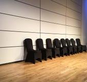 Μαύρες καλυμμένες καρέκλες ενάντια στον άσπρο τοίχο Στοκ Εικόνες