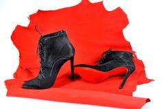 Μαύρες μπότες αστραγάλων γυναικών ` s χειροποίητες σε ένα κομμάτι του υλικού από το κόκκινο δέρμα Στοκ φωτογραφία με δικαίωμα ελεύθερης χρήσης