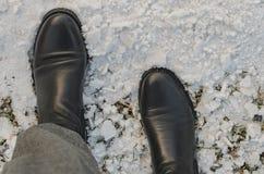 Μαύρες μπότες δέρματος στο χιόνι Στοκ Φωτογραφία