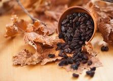 Μαύρες σταφίδες σε ένα ξύλινο κύπελλο Στο ξηρό φύλλο και την καφετιά ξύλινη ΤΣΕ Στοκ φωτογραφίες με δικαίωμα ελεύθερης χρήσης