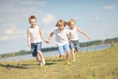 μαύρες χρωματισμένες παιδιά παίζοντας μορφές τρία ανασκόπησης Στοκ εικόνα με δικαίωμα ελεύθερης χρήσης