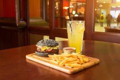 Μαύρες burger τηγανιτές πατάτες και ένα φλυτζάνι με τη σάλτσα ντοματών σε έναν ξύλινο πίνακα, με ένα ποτήρι της λεμονάδας μια φέτ Στοκ Εικόνες