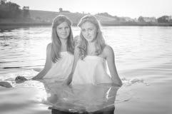 Μαύρη άσπρη φωτογραφία δύο ευτυχών κοριτσιών που παίζουν στο νερό στην παραλία ηλιοβασιλέματος Υπόβαθρο φλογών ήλιων Στοκ Φωτογραφία