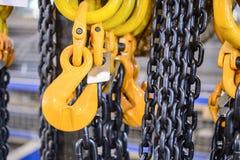 Μαύρη αλυσίδα χάλυβα και κίτρινοι γάντζοι φορτίου Στοκ Φωτογραφία
