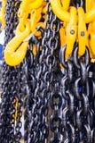 Μαύρη αλυσίδα χάλυβα και κίτρινοι γάντζοι φορτίου Στοκ Φωτογραφίες