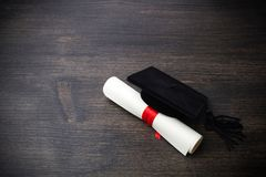 Μαύρη βαθμολόγηση ΚΑΠ με το βαθμό στο σκοτεινό ξύλινο υπόβαθρο στοκ φωτογραφία