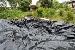 Μαύρη βινυλίου τρύπα κάλυψης φύλλων στο έδαφος που χρησιμοποιείται ως λίμνη στοκ εικόνα με δικαίωμα ελεύθερης χρήσης