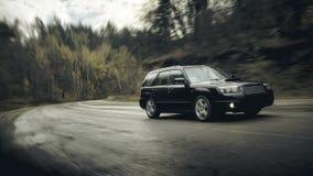 Μαύρη γρήγορη κίνηση αυτοκινήτων στο δρόμο ασφάλτου στην ημέρα Στοκ Εικόνες