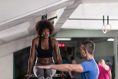 Μαύρη γυναίκα που κάνει την παράλληλη άσκηση φραγμών με τον εκπαιδευτή Στοκ εικόνες με δικαίωμα ελεύθερης χρήσης