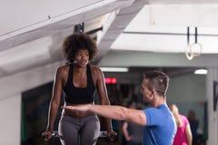 Μαύρη γυναίκα που κάνει την παράλληλη άσκηση φραγμών με τον εκπαιδευτή Στοκ εικόνα με δικαίωμα ελεύθερης χρήσης
