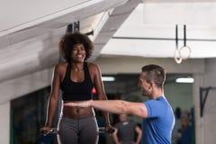 Μαύρη γυναίκα που κάνει την παράλληλη άσκηση φραγμών με τον εκπαιδευτή Στοκ φωτογραφίες με δικαίωμα ελεύθερης χρήσης