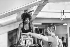 Μαύρη γυναίκα που κάνει την παράλληλη άσκηση φραγμών με τον εκπαιδευτή Στοκ φωτογραφία με δικαίωμα ελεύθερης χρήσης