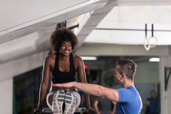 Μαύρη γυναίκα που κάνει την παράλληλη άσκηση φραγμών με τον εκπαιδευτή Στοκ Εικόνες