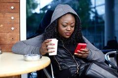 Μαύρη γυναίκα στον καφέ που έχει τον καφέ ενώ Texting Στοκ εικόνα με δικαίωμα ελεύθερης χρήσης
