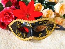 Μαύρη ενετική μάσκα με τις χρυσές διακοσμήσεις, λουλούδια στοκ εικόνα