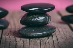 Μαύρη επεξεργασία πετρών σε έναν ξύλινο πίνακα μαύρο concept flower spa wellness πετσετών πετρών Στοκ Εικόνες