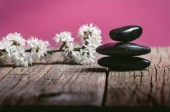 Μαύρη επεξεργασία πετρών σε έναν ξύλινο πίνακα μαύρο concept flower spa wellness πετσετών πετρών Στοκ εικόνες με δικαίωμα ελεύθερης χρήσης