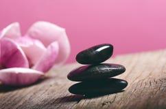 Μαύρη επεξεργασία πετρών σε έναν ξύλινο πίνακα μαύρο concept flower spa wellness πετσετών πετρών Στοκ φωτογραφία με δικαίωμα ελεύθερης χρήσης