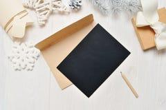 Μαύρη επιστολή ευχετήριων καρτών Χριστουγέννων προτύπων στο φάκελο και μολύβι, flatlay σε ένα άσπρο ξύλινο υπόβαθρο, με τη θέση γ Στοκ Φωτογραφία
