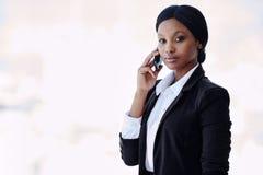 Μαύρη επιχειρηματίας που εξετάζει τη κάμερα κρατώντας ένα κινητό τηλέφωνο Στοκ Φωτογραφίες