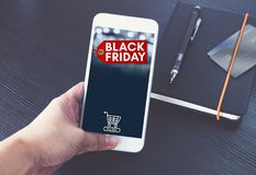 Μαύρη ετικέττα πώλησης Παρασκευής με το κάρρο αγορών στην κινητή οθόνη, χέρι χ Στοκ Φωτογραφία
