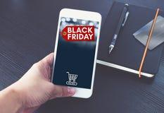 Μαύρη ετικέττα πώλησης Παρασκευής με το κάρρο αγορών στην κινητή οθόνη, χέρι χ Στοκ Εικόνες