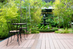 Μαύρη καρέκλα στο ξύλινο patio στον πράσινο κήπο με την πηγή στο εσωτερικό στοκ εικόνες