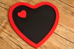 Μαύρη καρδιά πινάκων που διακοσμείται με μια κόκκινη καρδιά Στοκ φωτογραφία με δικαίωμα ελεύθερης χρήσης