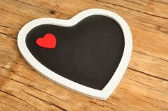 Μαύρη καρδιά πινάκων που διακοσμείται με μια κόκκινη καρδιά Στοκ εικόνα με δικαίωμα ελεύθερης χρήσης