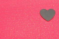 Μαύρη καρδιά που απομονώνεται σε ένα κόκκινο υπόβαθρο Στοκ Φωτογραφίες