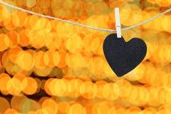 Μαύρη καρδιά που κρεμιέται στο σχοινί κάνναβης στο αφηρημένο ζωηρόχρωμο backgro bokeh Στοκ Εικόνες
