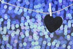 Μαύρη καρδιά που κρεμιέται στο σχοινί κάνναβης στο αφηρημένο ζωηρόχρωμο backgro bokeh Στοκ εικόνες με δικαίωμα ελεύθερης χρήσης