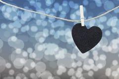Μαύρη καρδιά που κρεμιέται στο σχοινί κάνναβης στο αφηρημένο ζωηρόχρωμο backgro bokeh Στοκ φωτογραφία με δικαίωμα ελεύθερης χρήσης