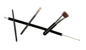 Μαύρη κορδέλλα βελούδου και τρεις βούρτσες makeup στο άσπρο υπόβαθρο Στοκ Εικόνες