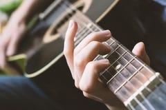 Μαύρη κλασική κιθάρα παιχνιδιού κοντά επάνω σε ετοιμότητα το fretboard και Στοκ Φωτογραφία