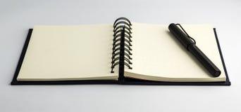 Μαύρη μάνδρα και κενό σημειωματάριο Στοκ Εικόνες