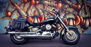 Μαύρη μοτοσικλέτα και ο τοίχος γκράφιτι Στοκ φωτογραφία με δικαίωμα ελεύθερης χρήσης