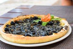μαύρη πίτσα Γίνοντας με τις σουπιές και τις μαύρες ελιές Στοκ φωτογραφία με δικαίωμα ελεύθερης χρήσης