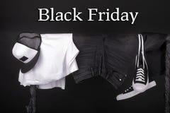 μαύρη Παρασκευή Κρεμώντας ιματισμός και άσπρα πάνινα παπούτσια, τζιν ΚΑΠ στο υπόβαθρο ραφιών ενδυμάτων Στοκ Εικόνες